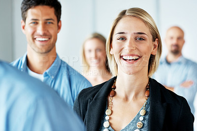 Buy stock photo Portrait of a happy young woman standing with collegues around