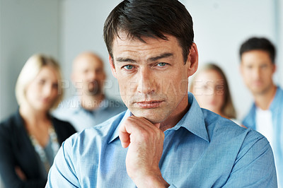 Buy stock photo Portrait of a handsome young businessman standing in office with colleague in background