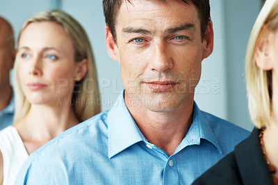 Buy stock photo Portrait of a handsome young businessman standing in a line with his colleagues at office