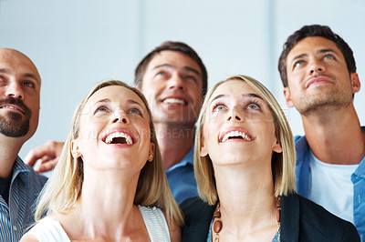 Buy stock photo Portrait of a happy young business team looking upwards at copyspace