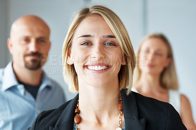 Buy stock photo Portrait of a confident young female smiling with her business colleagues at back