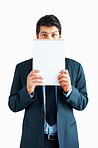 Executive with confused look while hiding behind notepad