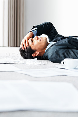 Buy stock photo Frustrated business man lying on the floor surrounded by paperwork - copyspace