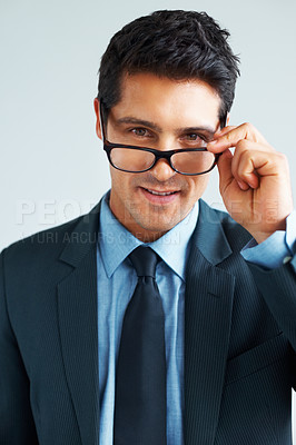 Buy stock photo Man in suit and tie holding rim of glasses on white background