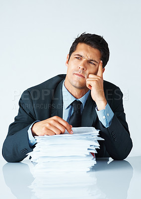 Buy stock photo Businessman contemplating options while sitting in front of paperwork