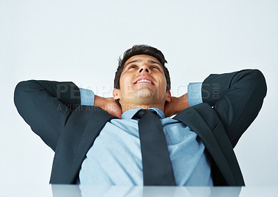 Buy stock photo Happy business man leaning back in chair with hands behind his head
