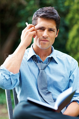 Buy stock photo Executive outdoors with book, looking frustrated