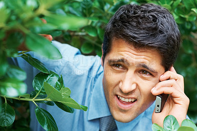 Buy stock photo Closeup of businessman hiding in bushes while on cell phone