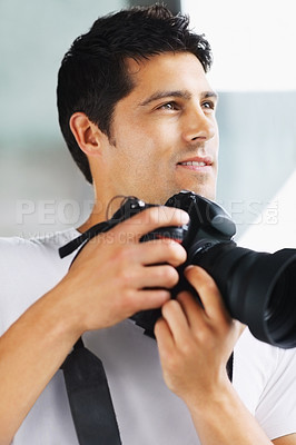 Buy stock photo Male photographer smiling while holding camera and looking outdoors