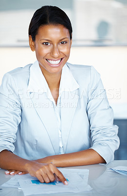 Buy stock photo View of female executive sitting at desk, reviewing paperwork