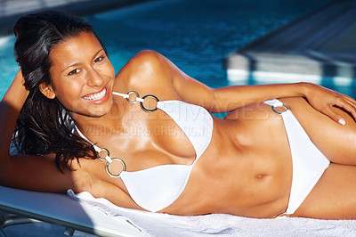 Buy stock photo Pretty woman lying on her side sunbathing nest to a swimming pool