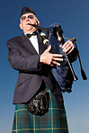 Mature highlander wearing kilt and playing bagpipes