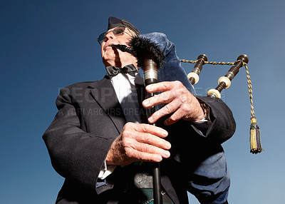 Buy stock photo Portrait of a mature highlander wearing kilt and playing bagpipes against sky