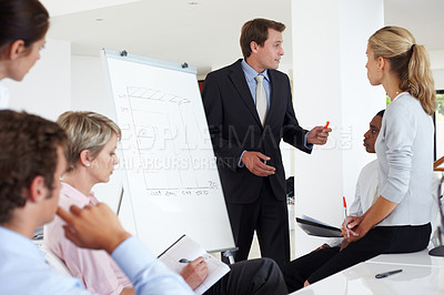 Buy stock photo Young businessman giving presentation to his colleagues during a meeting at office