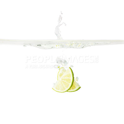 Buy stock photo Wedges of lime dropped into water against background