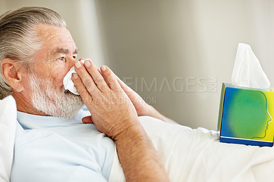 Buy stock photo Profile of a senior man blowing his nose while lying in bed