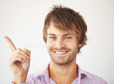 Buy stock photo Handsome young man smiling while pointing up