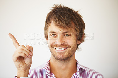 Buy stock photo Smart young man smiling while pointing up on white background