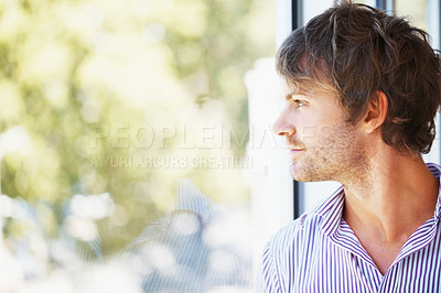 Buy stock photo Side view of young business man looking through glass window