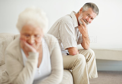 Buy stock photo Shot of an unhappy couple sitting on a sofa after an argument
