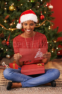 Buy stock photo Shot of an attractive young woman sitting with a gift and reading a Christmas card