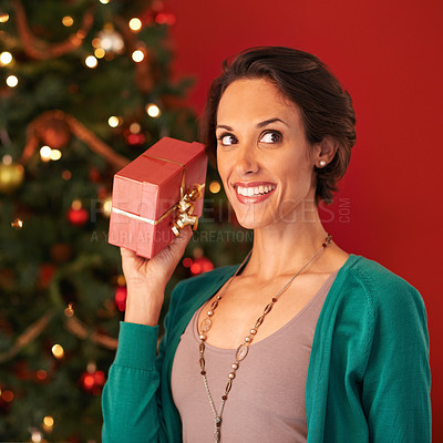 Buy stock photo Shot of an attractive young woman holding up her Christmas present to guess what it is