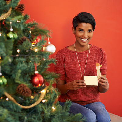 Buy stock photo Portrait of an attractive young woman opening her present by the Christmas tree
