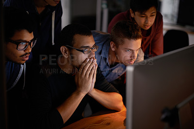 Buy stock photo Shot of a group of young designers staring tensely at a monitor