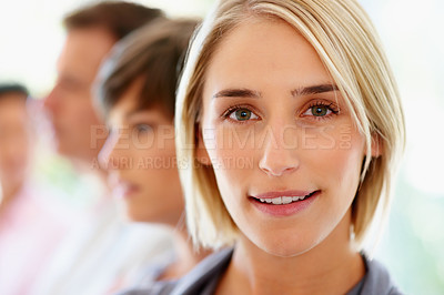 Buy stock photo Focus on blonde woman with team in distance