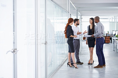 Buy stock photo Shot of businesspeople discussing paperwork in the office