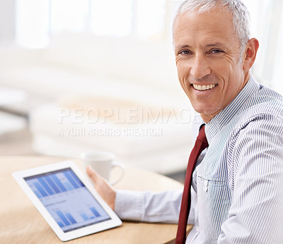 Buy stock photo Shot of a businessman looking pleased at the quarterly results he sees on his tablet