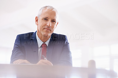 Buy stock photo Cropped shot of a mature businessman writing at a desk