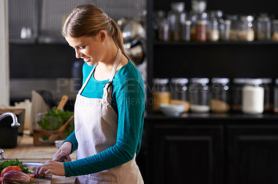 Buy stock photo Shot of an attractive young woman chopping vegetables at a kitchen counter