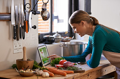 Buy stock photo Shot of a young woman looking at an online recipe on her digital tablet while preparing a meal