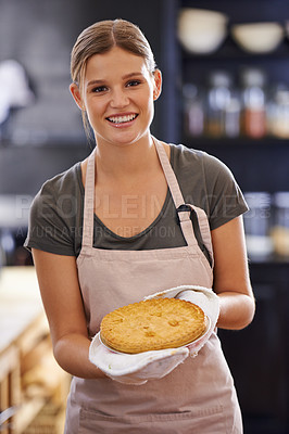 Buy stock photo Portrait of an attractive young woman standing in a kitchen holding a pie she baked