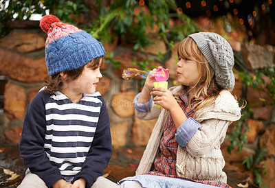 Buy stock photo Shot of two cute children blowing bubbles together outdoors