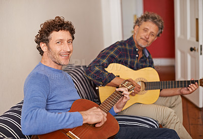 Buy stock photo Shot of a young man and his senior father playing guitar together indoors