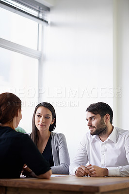 Buy stock photo Shot of a group of young business professionals in discussion around a table