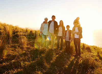 Buy stock photo A portrait of a happy family standing on a grassy hill at sunset