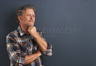 Buy stock photo A cropped shot of a thoughtful mature man standing against a grey background