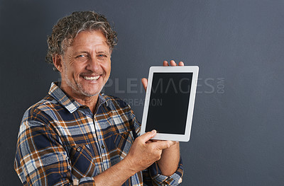 Buy stock photo A portrait of a happy mature man showing a tablet with a blank screen