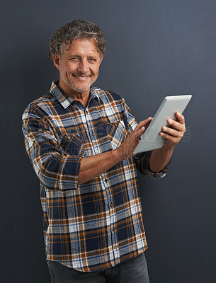 Buy stock photo A portrait of a happy mature man holding and using a tablet