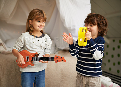 Buy stock photo Shot of two adorable siblings playing with their musical toys