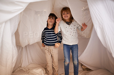 Buy stock photo Portrait of two adorable siblings jumping on the mattress underneath their fort