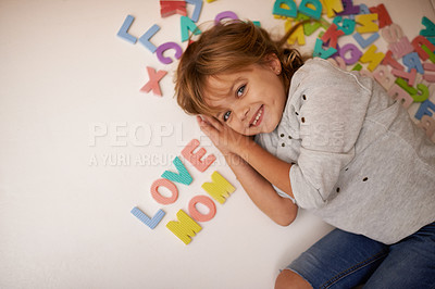 Buy stock photo Portrait of an adorable little girl lying next to toy letters which spell out the words