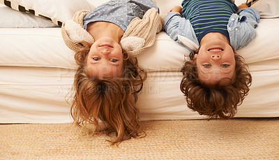 Buy stock photo Portrait of two young children lying on a sofa with their heads hanging over the edge