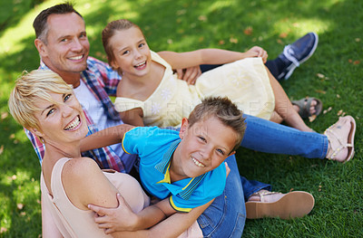 Buy stock photo A portrait of a happy family sitting on the grass together on a sunny day