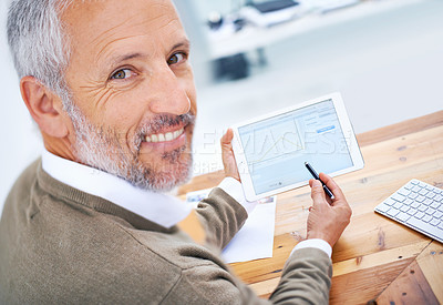 Buy stock photo A portrait of a happy businessman using a tablet at his desk