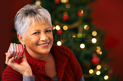 Buy stock photo Shot of a mature woman holding a christmas present to her ear