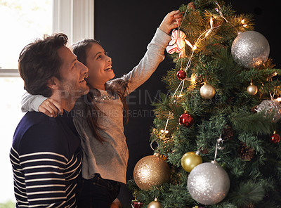 Buy stock photo Shot of a young girl and her father decorating the Christmas tree together